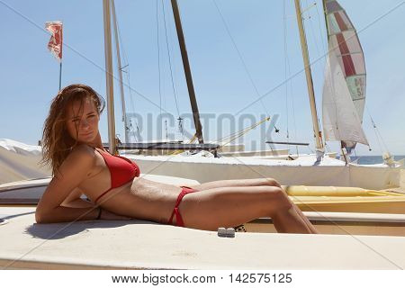 Photo Young Girl Making Chill Time Ocean Beach.Fitness Active Woman Spending Relax After Yaht Session Open Sea.Summer Season Race Concept. Horizontal Picture. Sails Boats Background