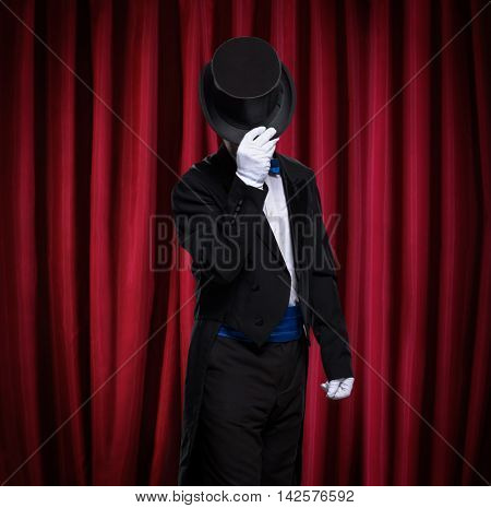 magician with top hat front red curtain on stage