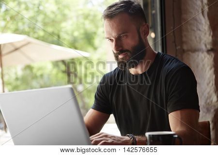 Concentrated Bearded Man Wearing Black Tshirt Working Laptop Wood Table Urban Cafe.Young Manager Work Notebook Modern Interior Design Loft Place.Coworking Process Business Startup.Color Filter