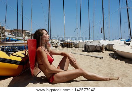 Photo Young Girl Making Chill Time Beach.Fitness Active Woman Spending Relax After Yaht Session Open Sea.Summer Season Race. Horizontal Picture. Boats Background