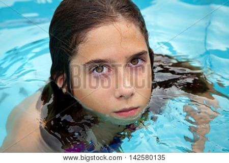 A tween girl seemingly growling at the camera. She does not want her picture being taken. Her eyes have dark circles under them and she has bushy eyebrows and a set jaw.