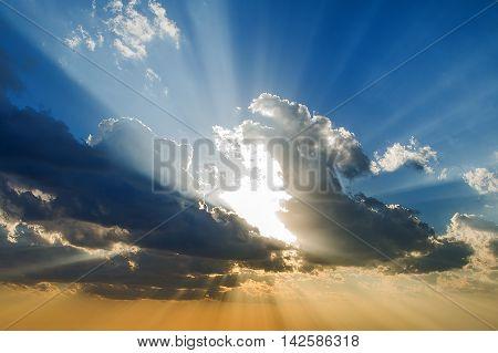 Sunlight breaks through the dark thunderstorm clouds