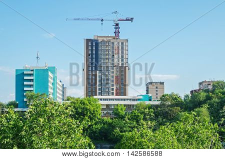 View of a skyscraper under construction from the thickets of a country park