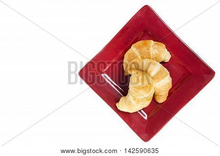 Three fresh flakey buttery croissants on a red plate and isolated on white with copyspace.