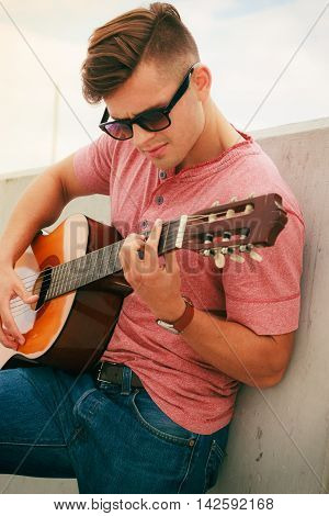 Performance and show on fresh air. Young fashionable man wearing sunglasses playing classic guitar outdoor. Summer time.