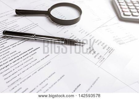 Pen and magnifying glass on finacial statement paper. Analysis business concept. Photo with sunlight filter effect.