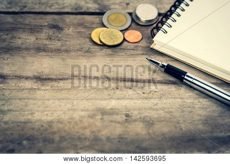 close up pen notepad and coins on wooden background with copy space. Financial planning concept. Selective focus with vintage tone photo.