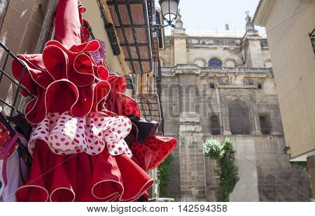 Street beside Granada Cathedral in the old town with shops selling souvenirs typical flamenco dresses Spain
