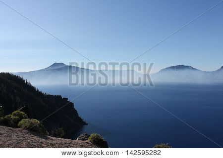 Smoke from a forest fire hovers over Crater Lake.