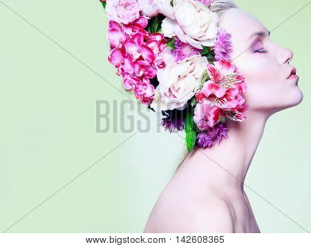 Beautiful girl, isolated on a light - green background with varicoloured flowers in hairs, emotions, cosmetics