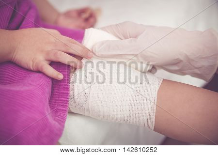 Child Injured. Pediatrician Doctor Bandaging Child's Knee. Vintage Tone Effect.