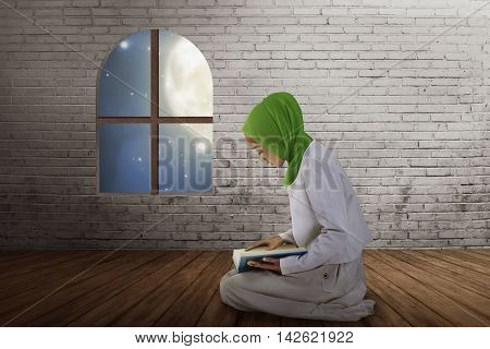 Young Muslim Asian Woman Reading The Quran