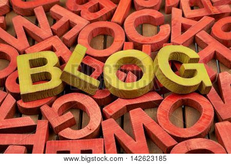 Word Blog made of green wooden block letters over the pile of red ones
