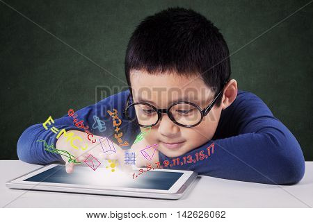 Photo of a little boy using a digital tablet to learn with formula of math on the screen