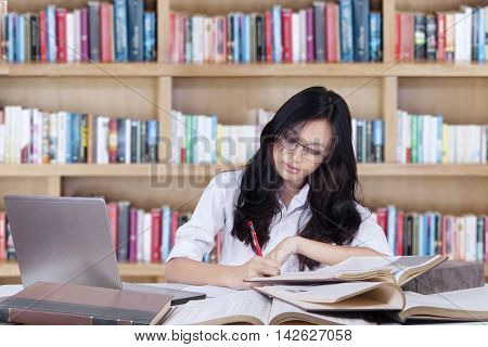 Portrait of a clever high school student with long hair studying in the library while doing her assignment
