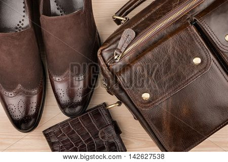 Classic brown shoes briefcase and purse on the wooden floor can be used as background