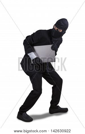 Male thief wearing mask and running while carrying a laptop computer isolated on white background