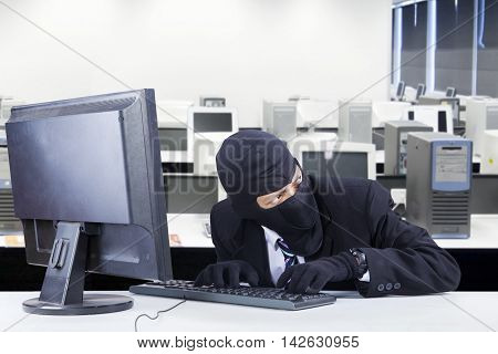 Male thief steals data on the computer while wearing mask and looking at around him in the office