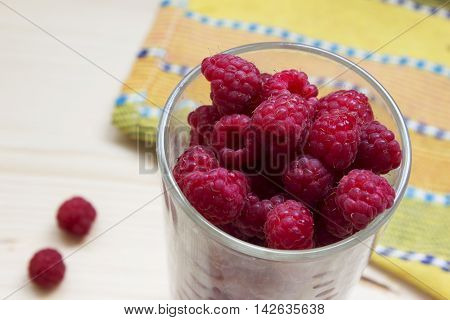Simmer fresh raspberries in a glass on a wood and yellow background