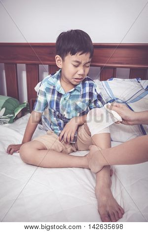 Crying child injured. Mother bandaging son's knee on bed inside bedroom bandage in focus asian boy sadden and crying. Human health care and medicine concept. Vintage tone effect.