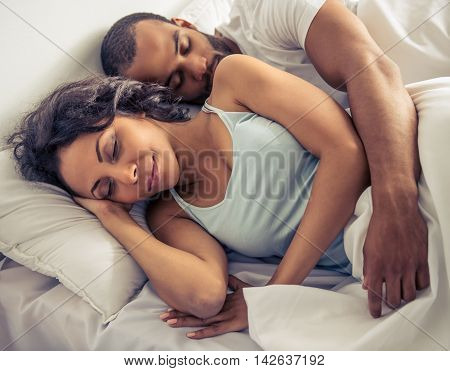 Beautiful young Afro American couple is sleeping in their bed at home