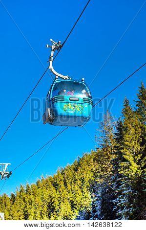 Bansko, Bulgaria - December 12, 2015: Close up Bansko cable car cabin, pine trees against blue sky, Bulgaria