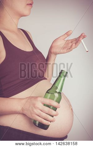 Side View Of Pregnancy With Cigarette And Alcohol. Pregnant Unhealthy Motherhood Concept. Vintage To
