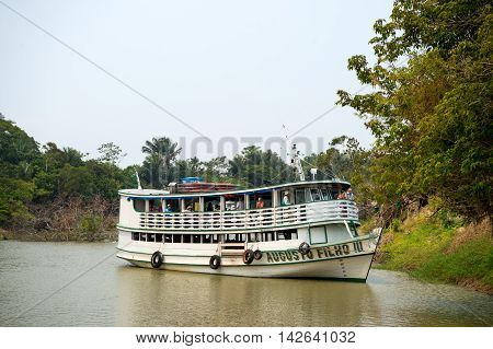 Amazon river near Santarem Brazil - -December 02 2015: white cruise boat with tourists on deck floating on dirty green river water near trees on coast on natural background