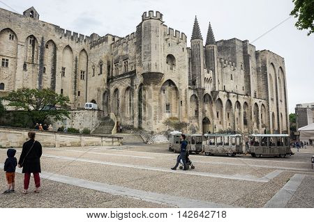 AVIGNON FRANCE - MAY 04 2015: Tourists on the square of Popes Palace Avignon. Popes Palace is the main historical site in Provence and one of the largest and most important medieval gothic buildings in Europe