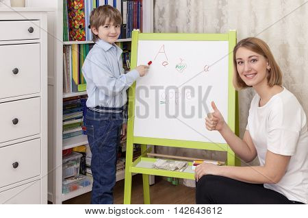 cute boy elementary school student meets lesson chalkboard. Beautiful young woman sitting next to the teacher. Smiling looking at the camera. Thumb up