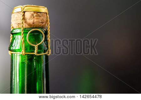 a green champagne bottle with cork closeup