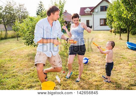 Little Boy With Mother And Father Splashing Each Other