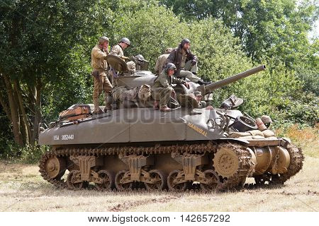 WESTERNHANGER, UK - JULY 25: Reenactors prepare to enter the fray on the allies side during a WW2 armoured battle reenactment at the War & Peace show on July 25, 2015 in Westernhanger