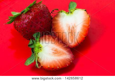 Fresh cleaved strawberry isolated on red background