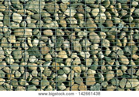 Pile Of Stones Behind Metal Grid.