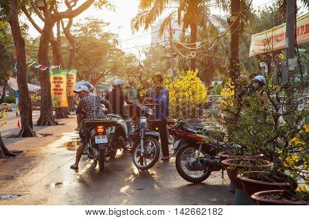 HO CHI MINH CITY VIETNAM - FEBRUARY 06: People buiying holiday trees at the street market during Tet or Lunar New Year celebrations in Ho Chi Minh City Vietnam on February 06 2016.