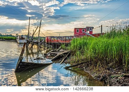 An old red fishing boat and broken docks along the shoreline of Shoal Harbor in Middletown NJ.