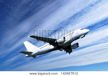 Airplane closeup.Travel background with airplane flying in the colorful blue sky. White flying airplane. Airplane in the sunlight. Closeup of flying airplane with blank livery.Airplane in the flight