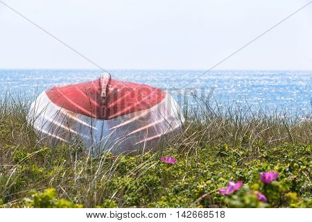 Red and white colored wooden boat upside down at the coast near the blue shiny sea