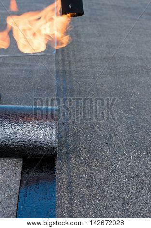 Professional installation of waterproofing on the concrete foundation. Roofer installing Roofing felt with heating and melting of bitumen roll by torch on flame during roof repair.
