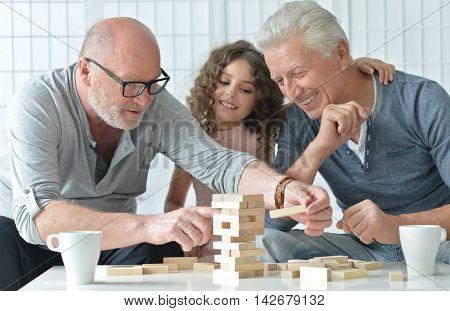 senior men and granddaughter having fun and playing board game at home