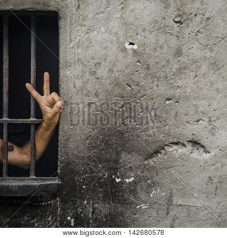 V sign (victory sign) a man behind bars. Background. Old worn unpainted smoke blackened the walls. Background.