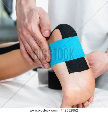 Physical Therapist Placing Taping On Patient's Foot