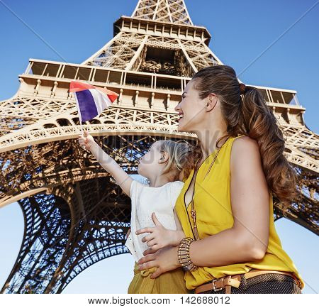 Mother And Daughter Travellers Rising Flag Against Eiffel Tower