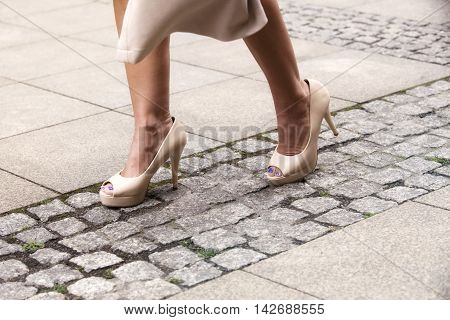 closeup of woman's feet with high heels walking in the street