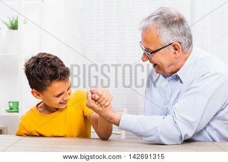 Grandfather and grandson arm wrestle at home.