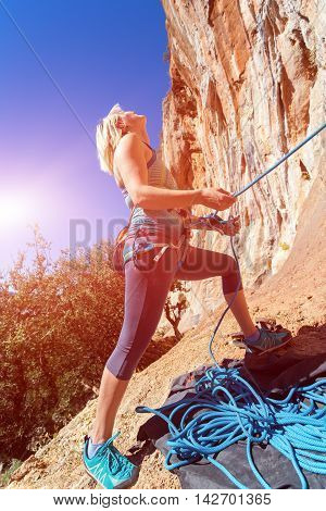 Blond Female Athlete belaying her Climbing Partner with Rope staying at orange rocky overhanging wall blue Sky and shining Sun