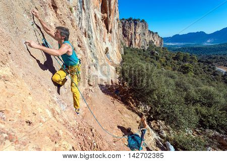 Team of Climbers Man and Woman ascending orange bright rocky Wall with rope and gear Male Leading Female belaying blue Sky and green Forest