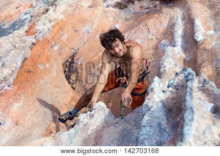 Top View of Smiling Climber naked torso bearded smiling and joyful face hanging high on rocky Wall and linking Rope into belay point