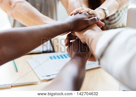 Multiethnic group of business people joining their hands together